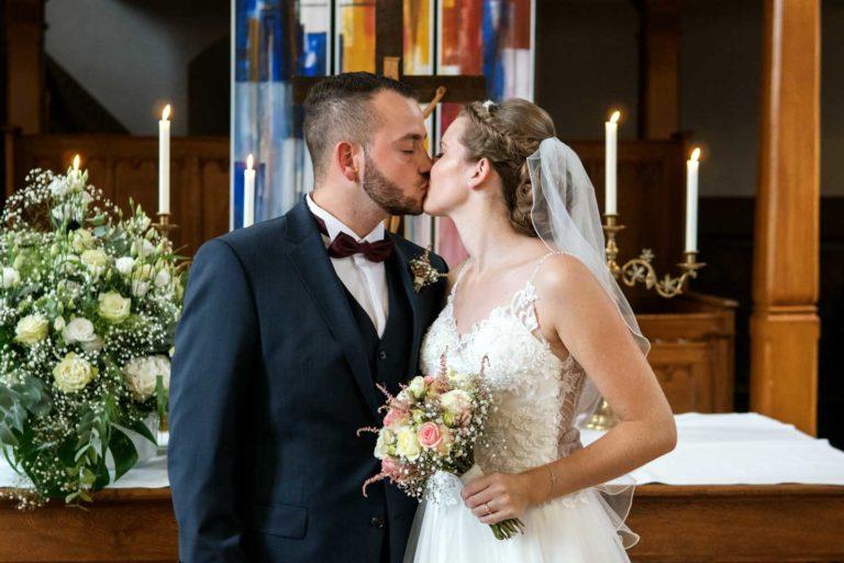 Hochzeitsfotograf | Brautpaar küsst sich vor Altar