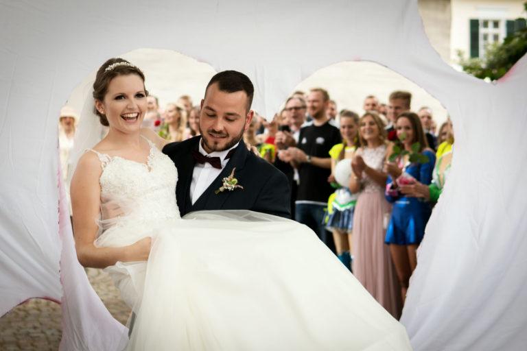 Hochzeitsfotograf | Bräutigam trägt Braut durch Herzwand